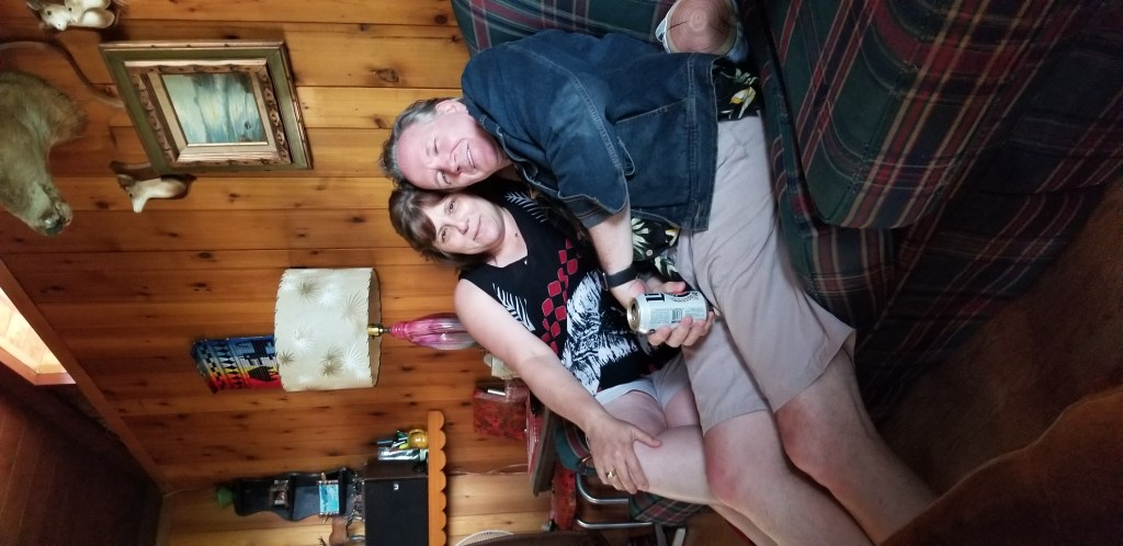Ed, wearing khaki shorts, a Hawaiian shirt and denim jacket, leaning into me, on a plaid couch with wood paneling in the background.