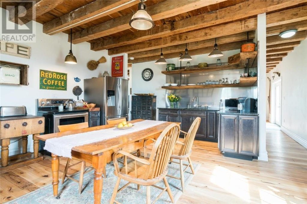 Kitchen. Cabinets are a deep blue. Big beams go across the ceiling. The light fixtures are period-correct and there are huge, wooden open shelves. Appliances are stainless steel.