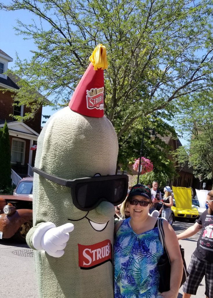 Me, and a pickle mascot that has sunglasses on and is giving a thumbs-up, on a busy street. It's sunny and you can see classic cars in the background.