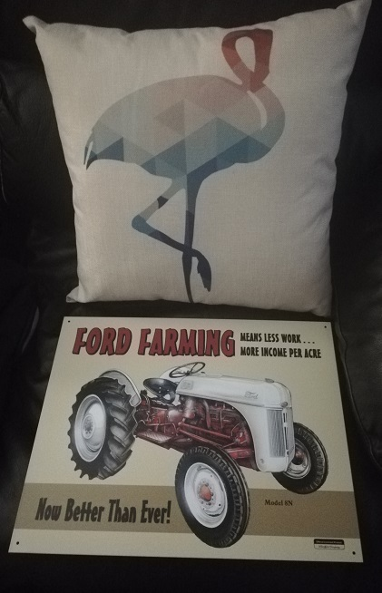 A canvas throw pillow with a pink and blue flamingo on it. A metal sign with a drawing of a Ford Ferguson tractor that reads Ford Farming means less work ...more income per acre.