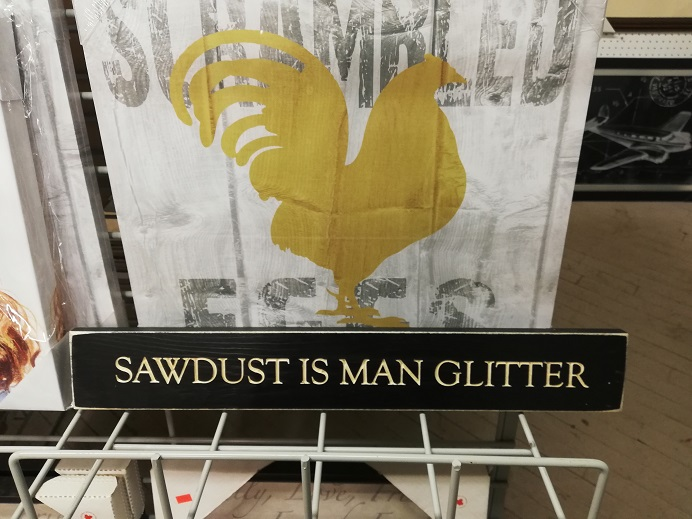 A sign with a painted chicken on it reads, Scrambled Eggs. In front of it, a long, short black sign that reads, in white, Sawdust is Man Glitter.