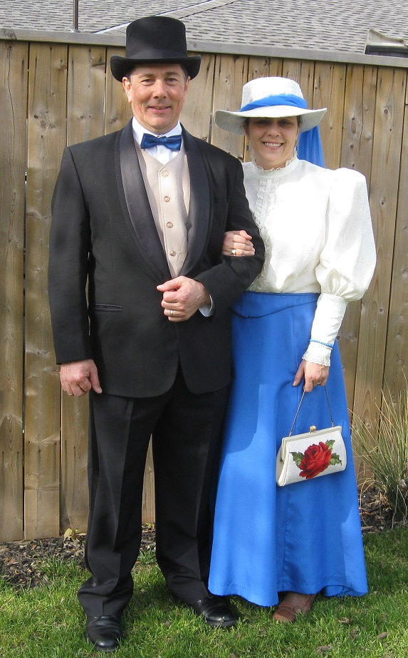 Derek and I posing outside. He's wearing a tux and top hat and I'm in a bright blue skirt, white blouse and white and blue hat, appropriate for 1912.