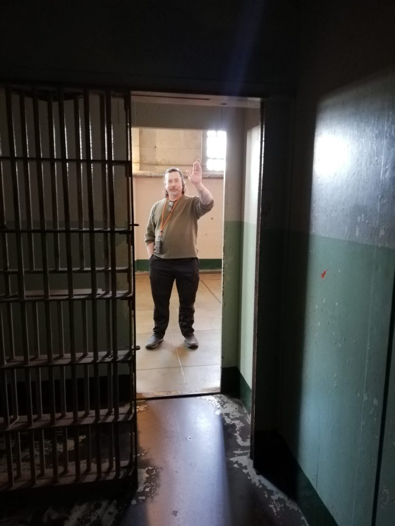 Derek waves into the small solitary confinement cell at Alcatraz. It has two sets of bars and a solid door which are all open and visible to the side.