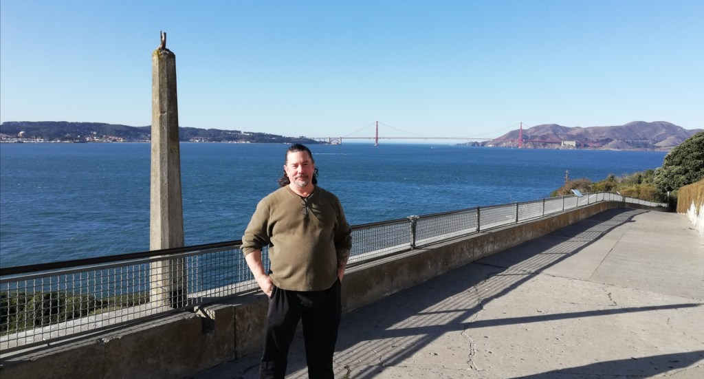 Derek poses near a railing along the water's edge at Alcatraz. The Golden Gate Bridge is in the background.