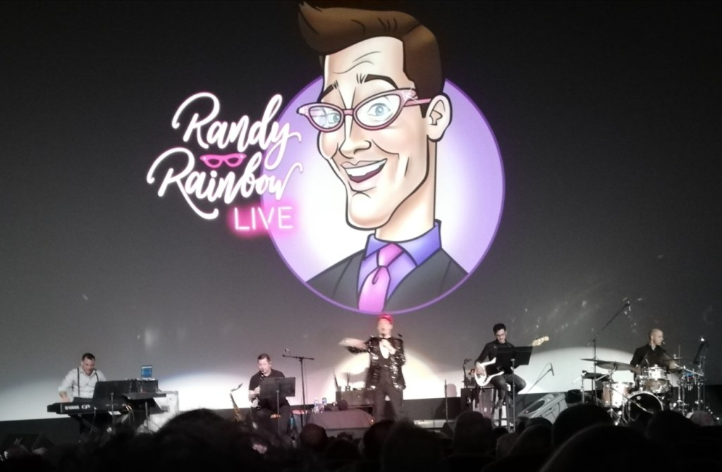 A shot of the stage with Randy's logo above, four musicians and Randy gesturing to the audience as he sings.