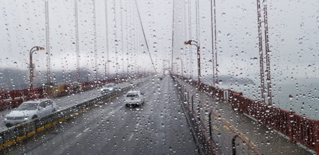A shot taken through the rain-soaked tour bus windshield shows our view ahead of the Golden Gate Bridge.