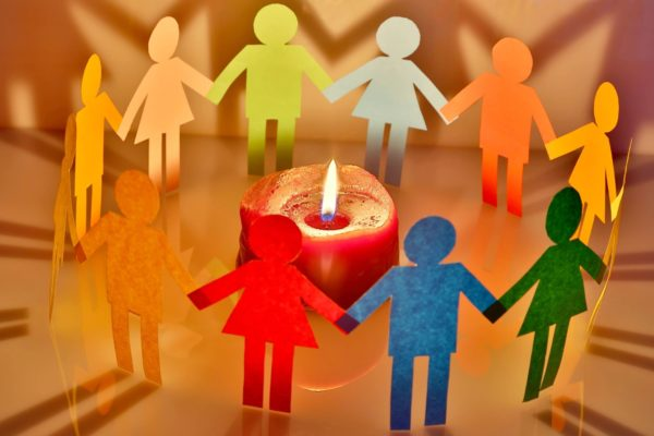 Little human figures cut out of different colour paper, joined in a circle around a candle