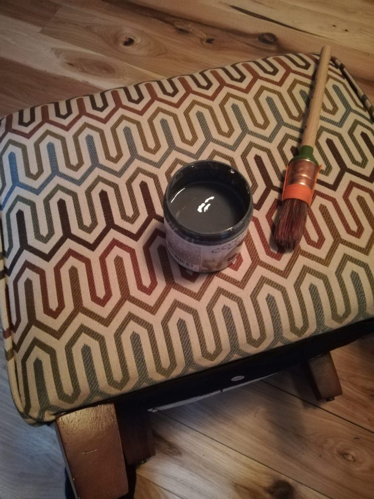 Ottoman on its side. It is beige with various shades of brown and rust geometric patterns. An open jar of dark grey paint and a brush sit on it.