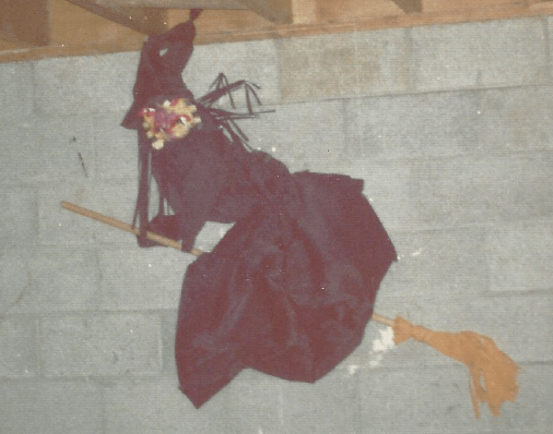 Large witch attached to the basement concrete block wall. It's wearing a black dress and flying on an actual broom affixed to the wall.