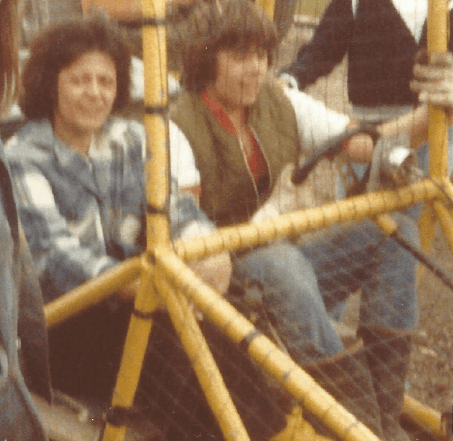 A bit blurry. An image of Mom and my brother Kevin behind the wire of a dune buggy as they prepare for a ride. Kevin is at the wheel.