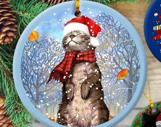 Smiling cat wearing a Santa hat and red plaid scarf in a snowstorm, on a round, blue ornament.