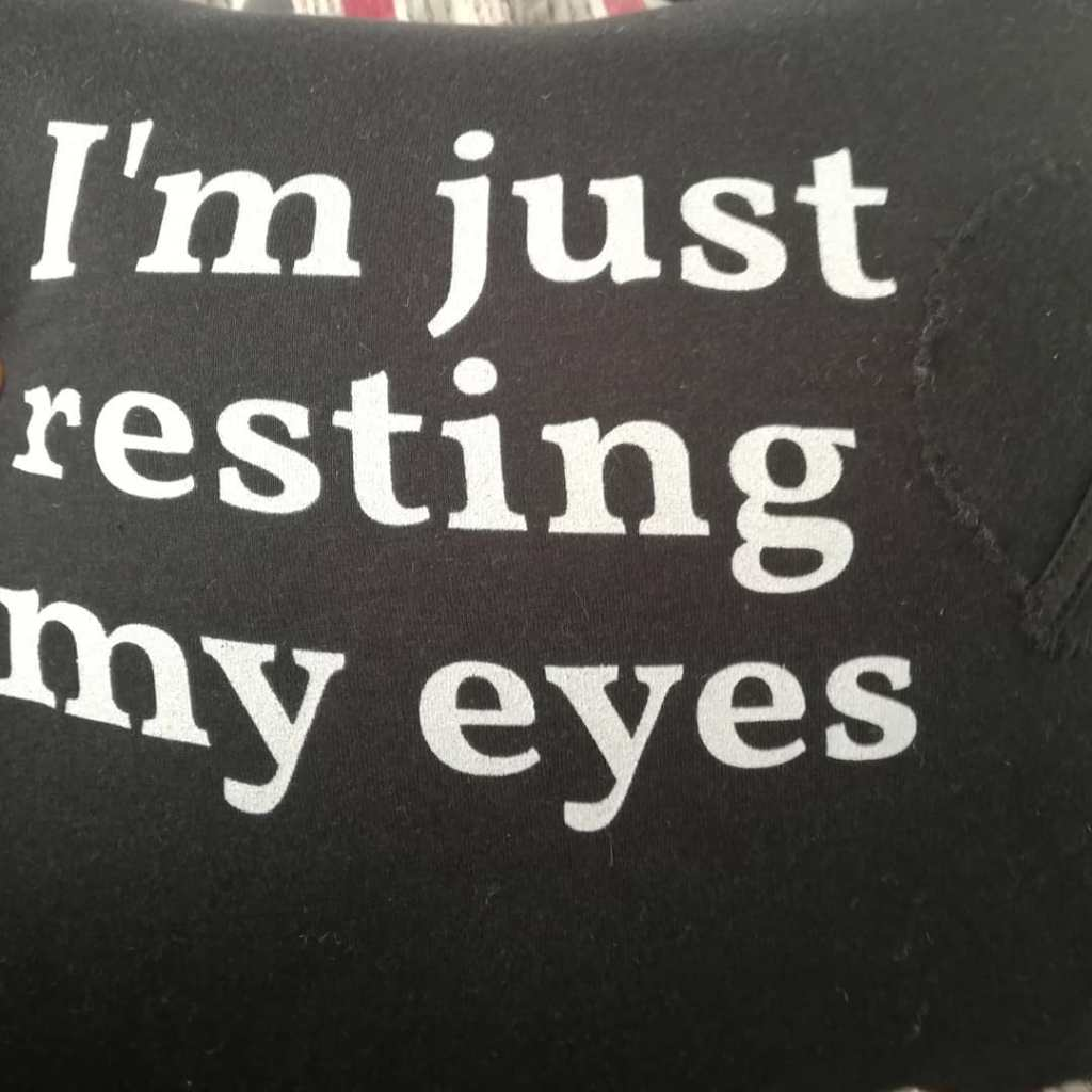 Black pillow with white lettering that reads: I'm just resting my eyes.