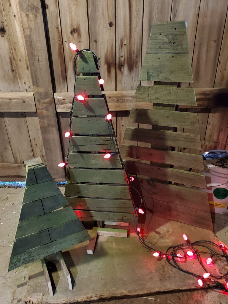 Three pallet trees in various sizes, standing up. A string of red Christmas lights outlines the medium sized tree and lays in a tangle on the ground.