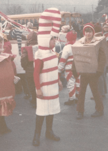 12-year-old me in a side view, wearing a white foam shell dress and a hat with red stripes. The hat curved down to my forehead, like a candy cane.