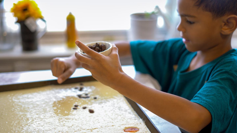 vera's son adding toppings to pancakes