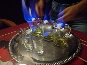 Three glasses with spoons balenced on them. both the green liquid and the sugar cubes on the spoon are on fire. the absinthe burns blue.