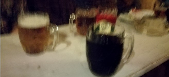 blurry picture of a table with drinks on. coke, beer and malinovka