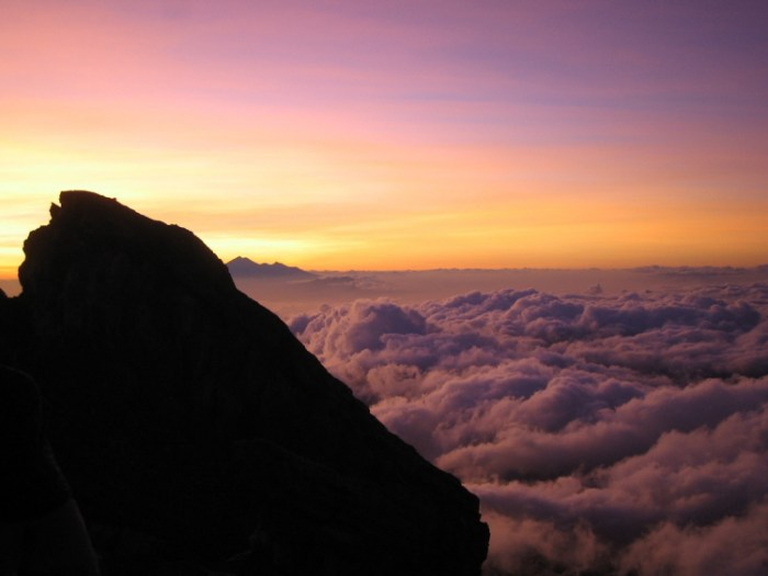 Sunset from the 3,148 m high summit of Gunung Agung. The peak in the distance is G. Abang, a remnant of a far loftier peak, Ancestral Batur. (WikimediaCommons, photo by Mrllmrll).