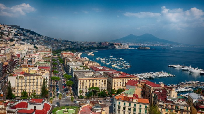 "Naples, formerly the capital of the ""Kingdom of the Two Sicilies"" before the unification of Italy in 1859-60, is a city with a rich cultural heritage that goes back more than 4,000 years. Today, it is the third largest city of Italy (after Rome and Milan) vibrant, carefree and, dare it be said, chaotic. 18 km from the vantage point of this photographer, Vesuvius looms over Naples, a constant reminder of danger. However, Vesuvius is perhaps the least dangerous of the three volcanic systems that threaten Naples. Behind the back of the photographer and 25 km away lies the volcanic island of Ischia. But between Ischia and the photographer, less than 5 km away, lies the potentially greatest threat of them all, Campi Flegrei. (city.samondeo.com)"
