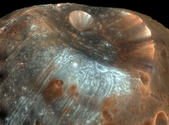 Enhanced image of the Martian moon Phobos and the giant crater Stickney. Phobos is not a proper moon as such but rather a captured asteroid measuring 27 × 22 × 18 km and its surface is one possible source for Helium-3, the helium isotope required for fusion and certain cryogenic applications. Phobos orbits Mars in 7 h 39.2 min at a distance of ~9,350 km, about 40 times closer than that of our own Moon. It's surface gravity is so low that a human wearing a space suit would only weigh about 75 grams, less than the weight of a new-born kitten on Earth. You could actually jump off into space from its surface. (Mars Reconnaisance Orbiter image taken on March 23rd, 2008. NASA/JPL)