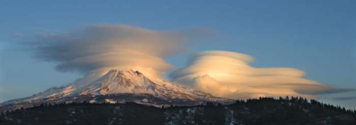 Mount Shasta often experiences strange weather phenomena. Here, Shasta is hidden by lenticular clouds whereas the cone of Shastina is clearly visible. Visible also in the foreground is the remains of the absolutely massive debris avalanche dated to between 300 and 380 kA that resulted from the collapse and total destruction of the ancestral cone. (summitpost.org)