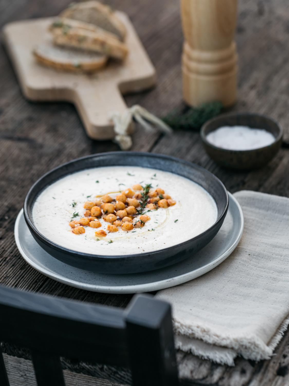 Cremige Blumenkohl Suppe mit gerösteten Kichererbsen und frischen Kräutern. Auf dem Holzuntergrund liegt ein weißes Tuch. Die Suppe ist in einer schwarzen Schüssel die auf einem weißen Teller steht. Im Hintergrund ist eine Pfeffermühle, Salz und ein Holzbrett mit Brotscheiben zu sehen.