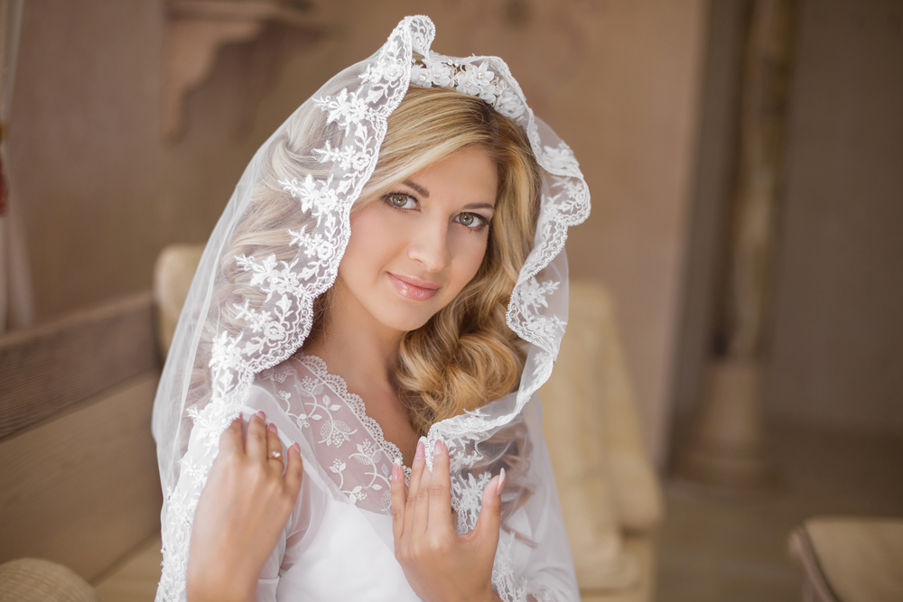 Beautiful smiling bride in wedding veil. Beauty portrait. Happy