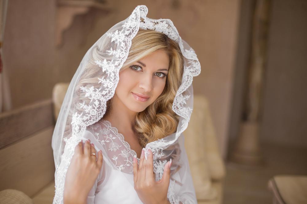 Beautiful smiling bride in wedding veil. Beauty portrait. Happy