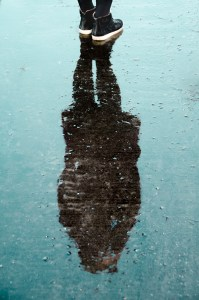 Feet and reflection of person in a puddle