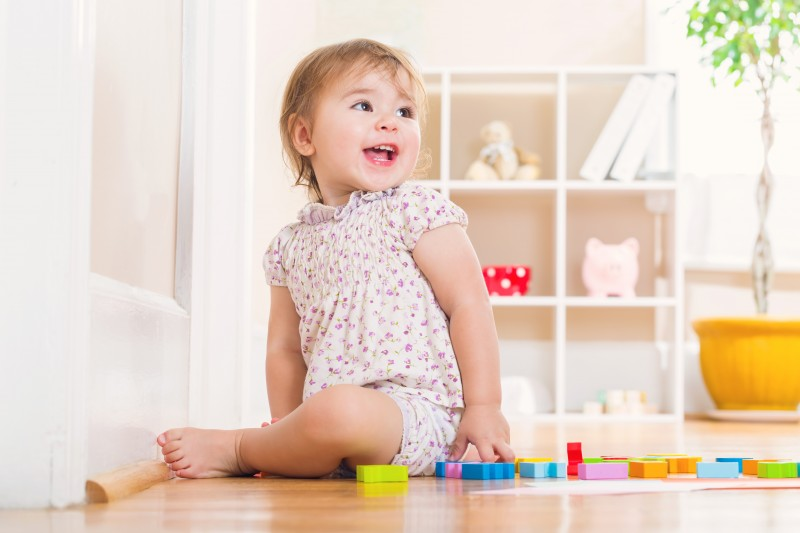Happy toddler girl with a big smile playing with wooden toy blocks inside her house
