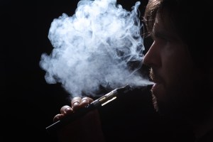 """Photo image of a """"Vape"""" or """"Cigarette"""" being used by a beard man with a cloud of smoke exiting his lips."""