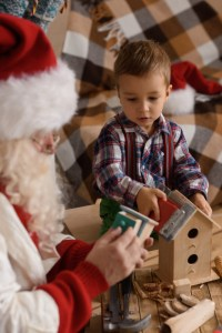 Photo of a child with Santa Claus working on a bird house.