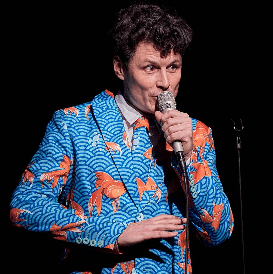 VONsociety: Manuel Rubey bei der Premiere seines Solo-Kabarettprogramms Goldfisch. Er steht auf der Bühne, hält ein Mikrofon in der Hand und trägt einen Sakko mit einem Muster, mit mittel- und hellblauem Wellenmuster und orangefarbenen Goldfischen, Krawatte im selben Muster und weißes Hemd © Ernesto Gelles