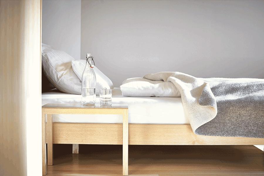 VONsociety: Nahaufnahme Zimmer im Hotel Post Bezau. Zu sehen ist ein Bett mit Holzgestell, weißen Bettbezügen und einer hellgrauen Überdecke aus Wolle. Vor dem Bett steht ein kleiner Holztisch, auf dem eine weiße Wasserflasche mit Kippverschluss und ein Wasserglas zu sehen sind. Die Wand im Hintergrund ist hellgrau gestrichen.