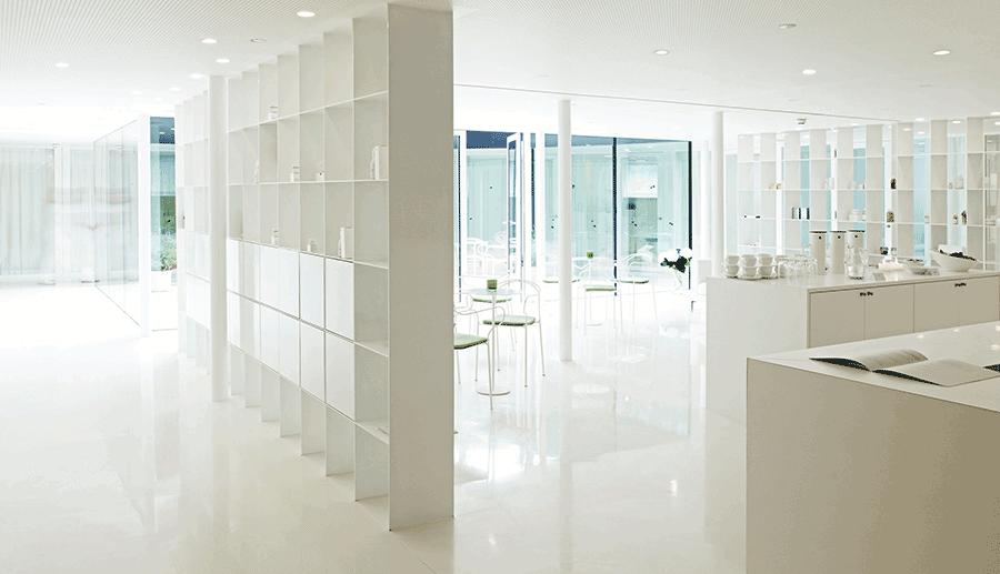 VONsociety: Ansicht des Wartebreiches im Spa des Hotel Post in Bezau. Alle Trennwände, der Boden und die Rezeption in weiß. Durch eine große Glaswand kommt Sonnenlicht in den Raum