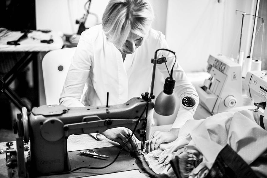 VONsociety: schwarz-weiß Aufnahme von Bettina Grieshofer. Sie sitz an der Nähmaschine und arbeitet an einem Dirndl