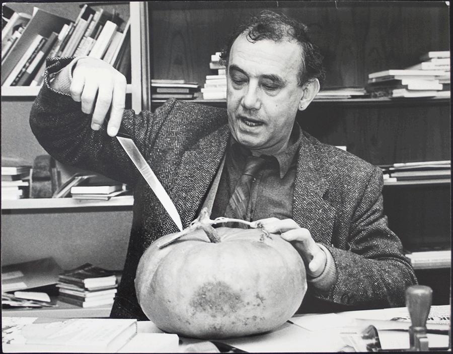VONsocieety: schwarz-weiß Foto von Daniel Spoerri an der Kunstakademie München ca. 1982. Er hat einen Kürbis vor sich, hält ein Messer in der rechten Hand, und setzt an, damit in den Kürbis zu stechen.