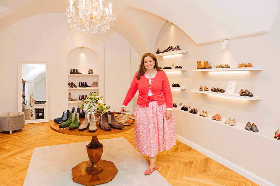 VONsociety: BELLAS Vienna Gründerin Jeannette Mang zu sehen in ihrem neuen Store. Sie steht neben einem runden Holztisch, auf dem Chelsea-Boots und Ballerina präsentiert werden. Sie trägt einen rosa-weiß gemusterten langen Rock und eine einfärbige rosa Strickweste und rosa Tassen Loafers. An den weiß gestrichenen Wänden sind Regalbretter montiert auf deinen die unterschiedlichen Schuhmodelle präsentiert werden. In der Mitte des Raumes hängt ein Kristallluster