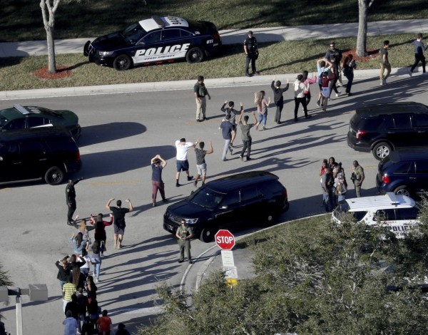 FILE - In this Feb. 14, 2018 file photo, students hold their hands in the air as they are evacuated by police from Marjory Stoneman Douglas High School in Parkland, Fla., after a shooter opened fire on the campus.  (Mike Stocker/South Florida Sun-Sentinel via AP, File)