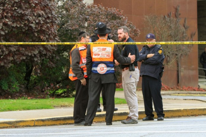 Police officers guarding the Tree of Life synagogue following shooting at the synagogue, speak with men in orange vest from a Jewish burial society in Pittsburgh, Pennsylvania, U.S., October 27, 2018.   REUTERS/John Altdorferâ?¨
