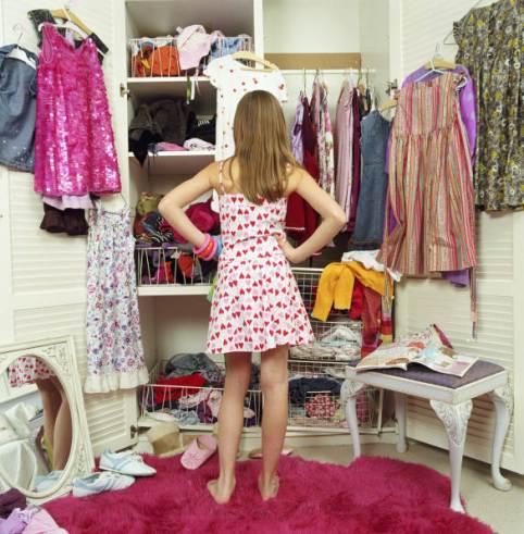 Jeune femme face à son armoire pleine