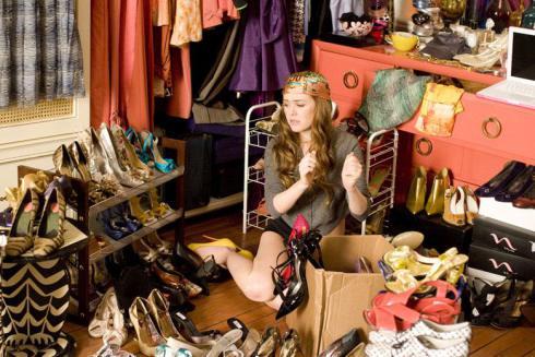 Jeune femme perdue au milieu de ses vêtements et accessoires