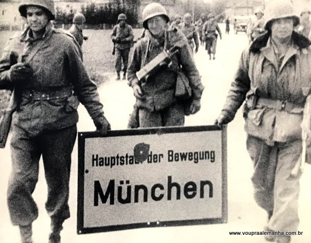 """Foto capturada na exposição do Centro de Documentação Nazista, em Munique, na qual soldados norte-americanos retiram a placa """"Munique, Capital do Movimento"""" da cidade."""