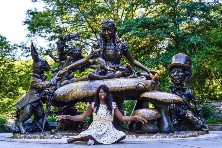 Nath devant la statue de bronze d'Alice aux Pays des Merveilles à Central Park - New York, Etats-Unis