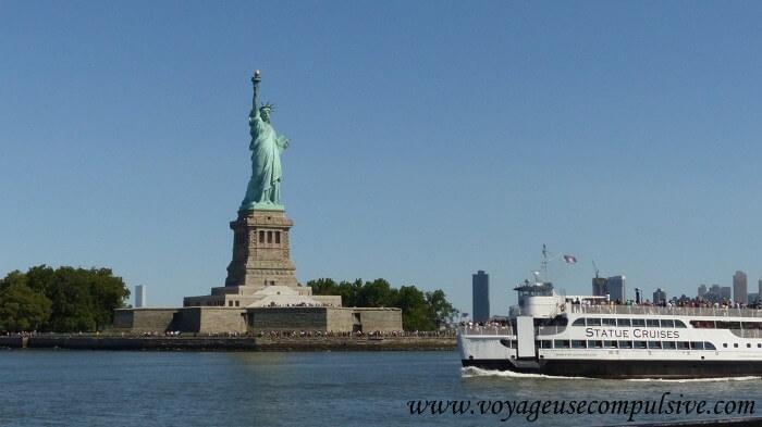 Vue sur l'un des bateaux de la compagnie Statue Cruises qui passe devant la statue de la liberté