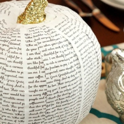 A personalized book page covered pumpkin creates a special gratitude-filled centerpiece for Thanksgiving