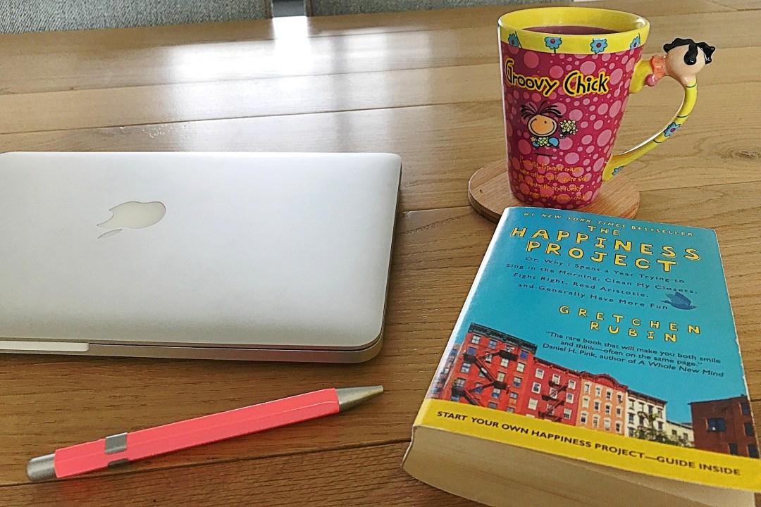 """Boek """"The Happiness Project"""", een pen, een macbook en een kopje thee op de eettafel"""