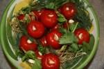 Укладываем помидоры в банку или миску, перекладывая крупно нарезанной травой