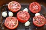 Помидоры нарезаем на половинки и кладем в глубокое блюдо для запекания разрезанной частью кверху