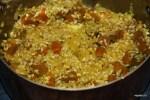 Добавляем в обжаренный лук рис и половину порции тыквы